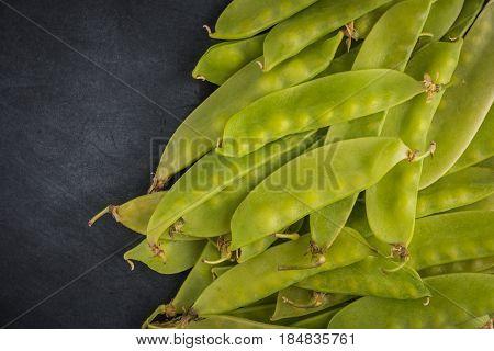 Fresh snow peas on slate background. Healthy food