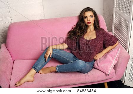 Fashionable classy stylish girl in blue jeans and purpple pullover sitting at pink sofa. Stunning beautiful pretty girl with long curly hair and red lips looking at you