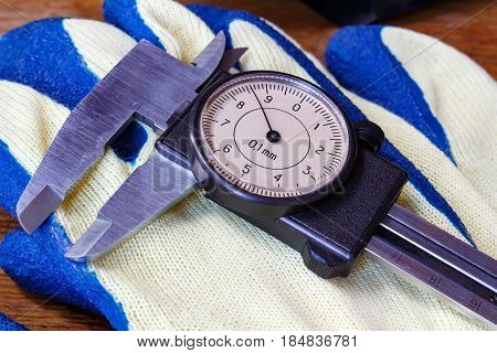 Slide caliper with round dial on a working glove