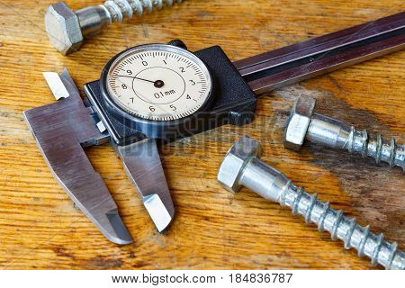 Slide caliper with a round dial on the table in workshop