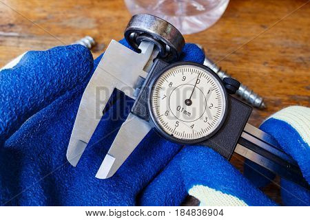 Measurement of the ball bearing inner diameter by a master in gloves with a slide caliper
