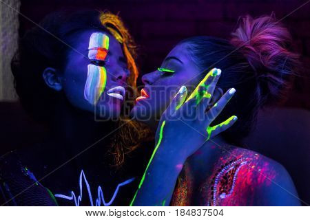 Sexy lesbian fashion models in uv neon light with fluorescent glowing Body Art make-up kissing. Low key dark image. Soft focus image.