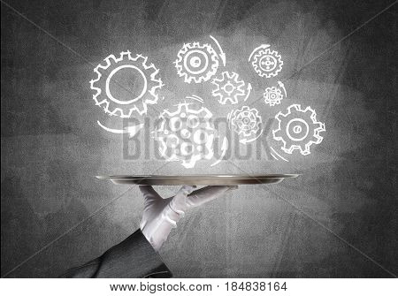 Butler holding metal tray with teamwork concept against concrete background