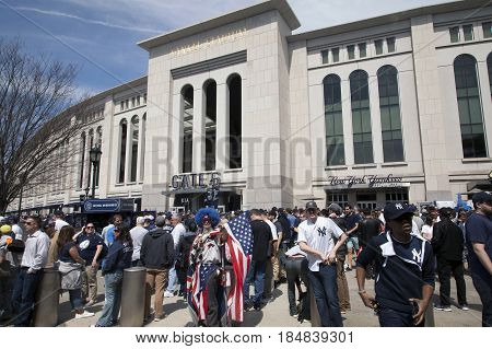 BRONX NEW YORK USA - APRIL 10: Flag bearing Lenny Love and fans stand outside Yankee Stadium on opening day. Taken April 10 2017 in New York.