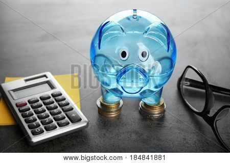 Composition of piggy bank, coins, glasses and calculator on grey table