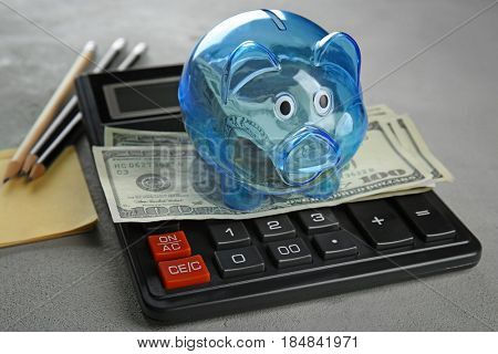 Composition of piggy bank with dollars, stationery and calculator on grey table