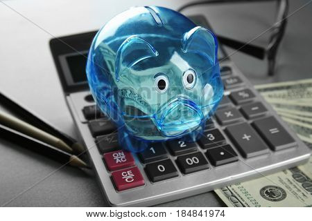 Composition of piggy bank with dollars and calculator on grey table