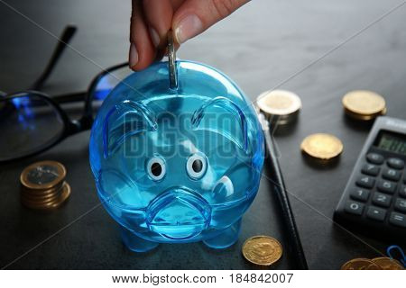 Female hand putting coin into piggy bank on grey table