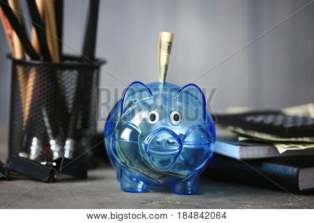 Composition of piggy bank with dollars and stationery on grey table