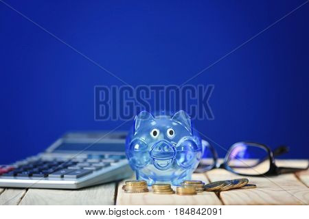 Composition of piggy bank and coins on wooden table