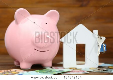 Savings concept. Piggy bank with money and house figure on wooden table