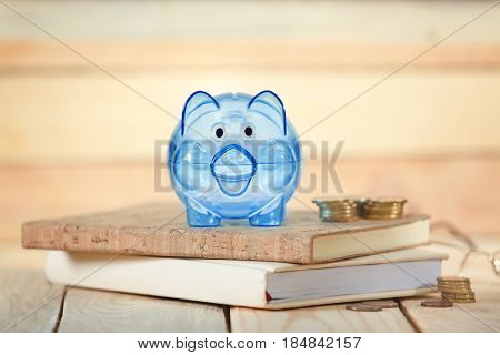 Composition of piggy bank, coins and notebooks on wooden table