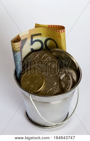 Fifty Australian dollars with coins in a bucket.