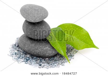 Three balancing zen stones stacked with wet leaves on small glass like pebbles isolated against a white background