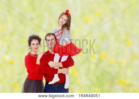 Happy young family dad mom and a little girl in bright red outfits . Dad holds daughter on hands.Summer white green blurred background.