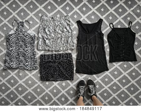 Choice of stylish black and white clothes on the floor woman standing near it.