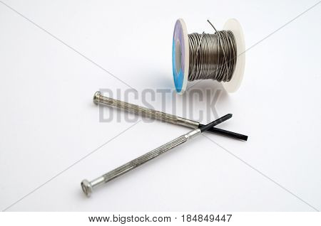 Gray screwdrivers next coiled tin on a white background