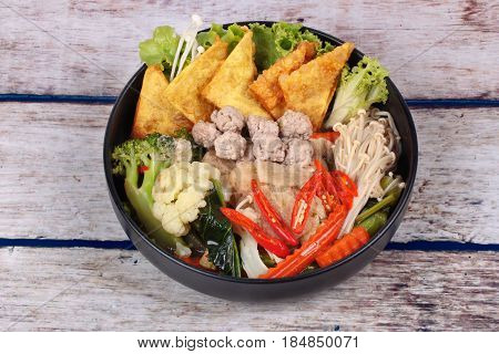 Chinese food Crisy wonton and meat ball in Chinese kale soup with carrotcorn golden needle mushroomcauliflowerbamboo mushroom and red chili call Kaew Krob Rad Naa in Thai. poster