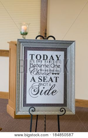 Sign reads today as two families become one we ask that you choose a seat not a side at a wedding ceremony in a traditional church.