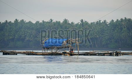Floating fishing hut, Davao Oriental, Philippines A floating fishing ccottage in the middle of the lagoon with blue tent in Puntalinao fishing village, Davao Oriental