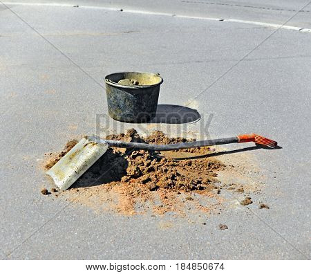 Metal scoop shovel on pile of sand and bucket with mortar on asphalt near site of roadwork