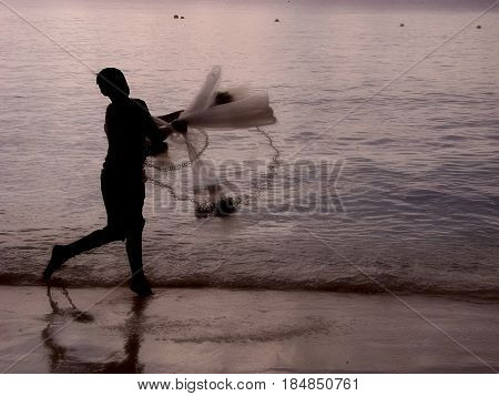 Silhouette of a fisherman  A fisherman is silhouetted throwing out a fishing net at the seaside at twilight.