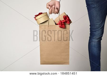 closeup of a young caucasian man carrying a paper shopping bag full of gift boxes ornamented with red ribbon against an off-white background, with a blank space in the bag