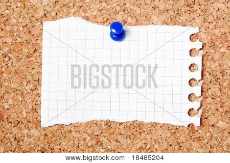 Blank scrap of notepaper pinned to cork noticeboard.