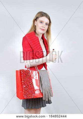 Young smiling girl holding a red shopping bag