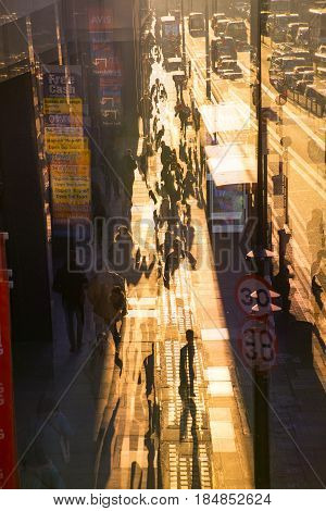 London, UK - November 30, 2016: Multiple exposure image of the York road at sunset. Buses, cars and walking people against of sun.