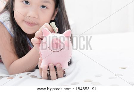 cute girl hand put money to piggybank on bedroom concept saving for education.