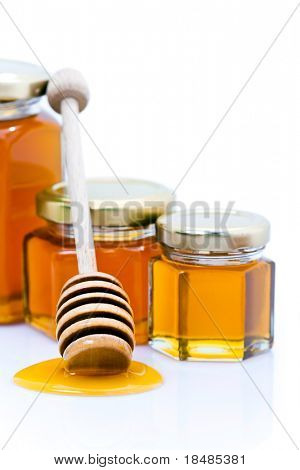 Dipper with honey in front of three different sized glasses isolated on white studio background.