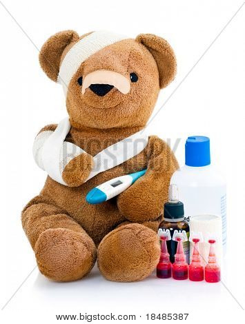 Sick teddy bear wrapped in bandages with underarm thermometer and bottles of medicinal drugs, isolated on white background.