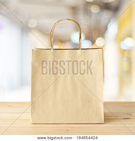 Brown paper shopping bag on wood table over blurred store background business template retail sale