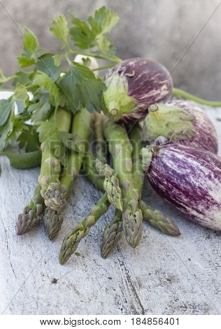 Fresh green asparagus and eggplant on old wooden table