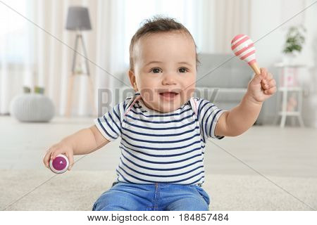 Cute little baby with rattles at home
