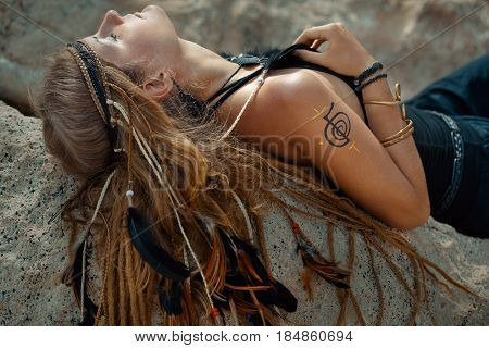 young beautiful boho woman on the rocks