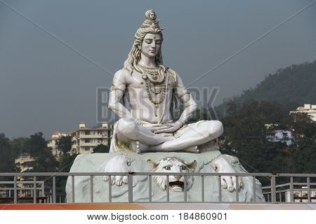 Hindu lord Shiva sculpture sitting in meditation on Ganges river in Rishikesh India 2011