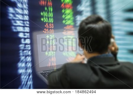 Motion blur of trader with computer in the marketing room on blurred stock board background in business concept