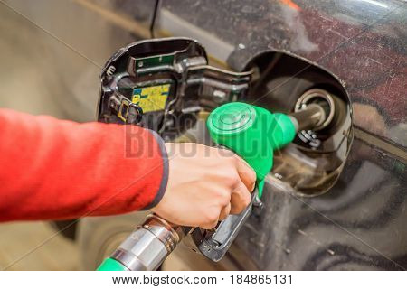 Hand refilling the car with fuel at filling station
