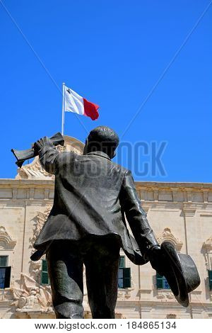 VALLETTA, MALTA - MARCH 30, 2017 - Statue of Manuel Dimech in Castille Square with part of the Auberge de Castille (office of the Prime Minister) to the rear Valletta Malta Europe, March 30, 2017.