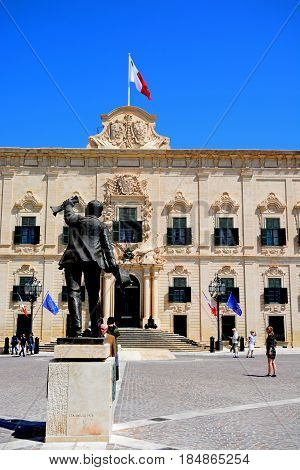 VALLETTA, MALTA - MARCH 30, 2017 - Statue of Manuel Dimech in Castille Square with the Auberge de Castille (office of the Prime Minister) to the rear Valletta Malta Europe, March 30, 2017.