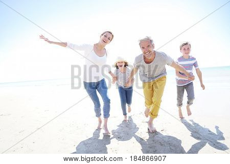 Happy family of four walking on sandy beach