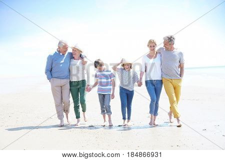 Family, parents, grandparents and grandkids walking on the beach