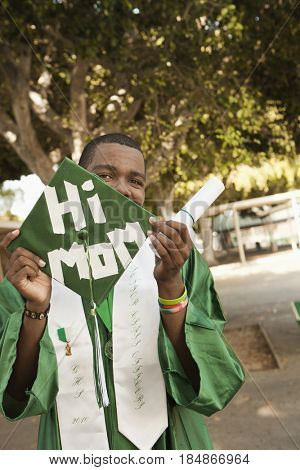 Smiling mixed race high school graduate with cap that says 'hi mom'