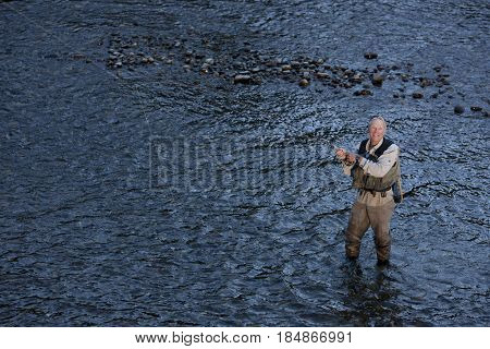 Caucasian man fly-fishing in river