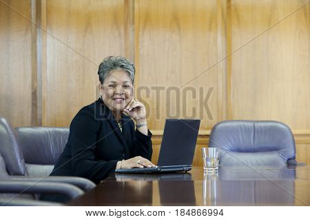 African American businesswoman using laptop in conference room