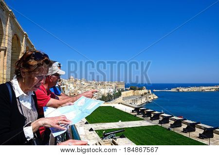 VALLETTA, MALTA - MARCH 30, 2017 -  Tourists looking at a map overlooking The Noon Gun in the Saluting Battery seen from the Upper Barrakka Gardens Valletta Malta Europe, March 30, 2017.