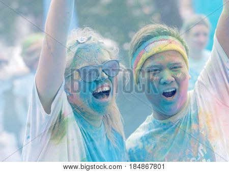 STOCKHOLM SWEDEN - MAY 22 2016: Teenagers covered with color dust rasing arms in the air in the Color Run Event in Sweden May 22 2016