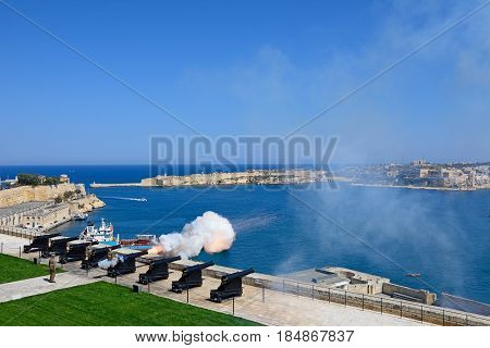 VALLETTA, MALTA - MARCH 30, 2017 - The Noon Gun in the Saluting Battery seen from the Upper Barrakka Gardens with views over the bay towards Fort Rikasoli Valletta Malta Europe, March 30, 2017.